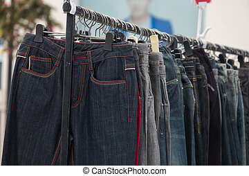 Row of Jeans and trousers on hangers for sale.