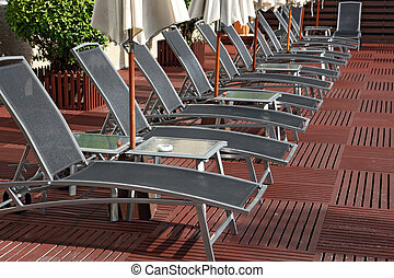 Lounge chairs - Row of Lounge chairs and Umbella surround a...