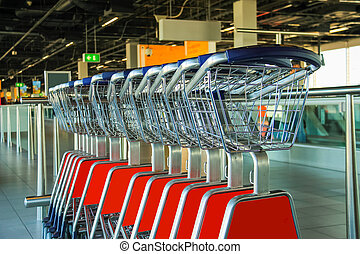 Row of luggage carts in hall of the airport