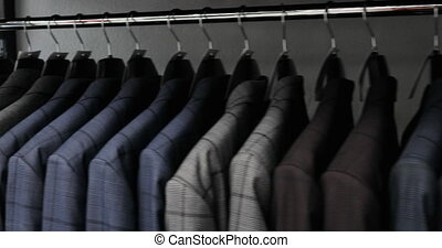 Row of men suit jackets on hangers. Collection of new...