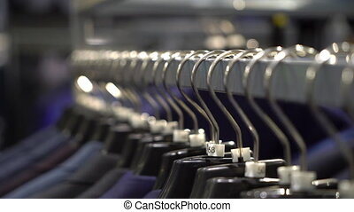 Row of men suit jackets on hangers in a shop