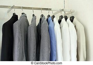 Row of men's suit jackets hanging in shop