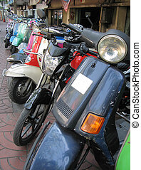 Row of mopeds on a street of Bangkok