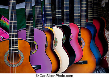 Row of multi-colored Mexican guitars - A row of various...