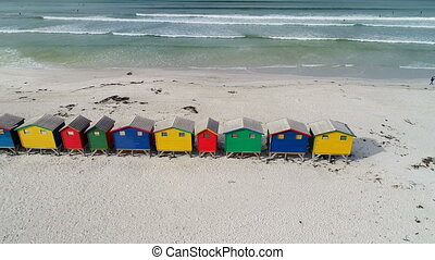 Row of multicolored beach huts on the beach 4k - Aerial of...