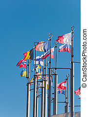 Row of national flags against blue sky