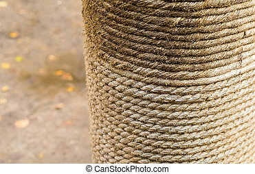 row of natural beige rope horizontal row wound on a log close-up a column with jute on a blurry ground background
