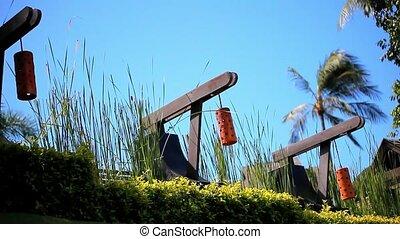 Row of orange Japanese lantern on blue sky, palms and grass...
