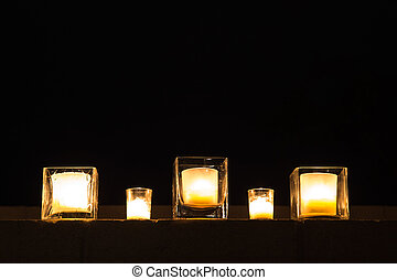row of outdoor candles at night