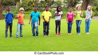 Row of cute pupils racing on the grass outside the elementary school