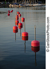 Row of red bouys reflecting in the water