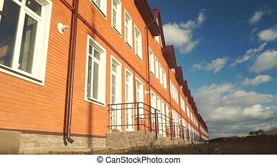 Row of red brick townhouses on a sunny day
