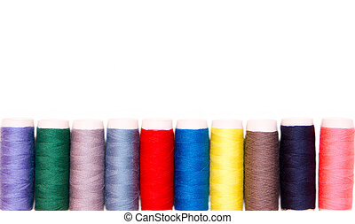 Row of sewing thread in different colors on white background