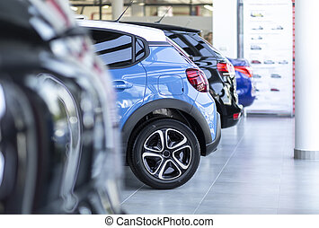 Row of shiny cars for sale parked in a showroom interior