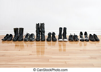 Row of black shoes and boots on a wooden floor, in front of a white wall.