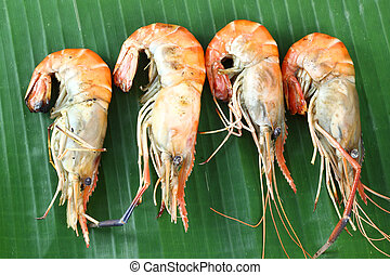 Row of shrimp grilled on banana leaf.