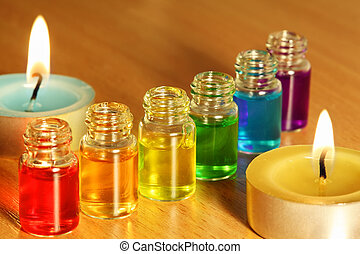 Row of six bottles with colored aroma oils and two candles...