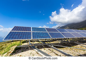 Row of solar collectors on mountain with blue sky