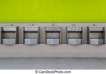 Row of stainless steel urinals in public toilets