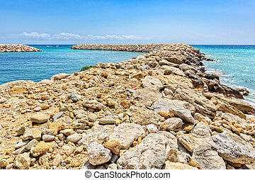 Row of stones as weir in greek sea - Row of rocks and stones...