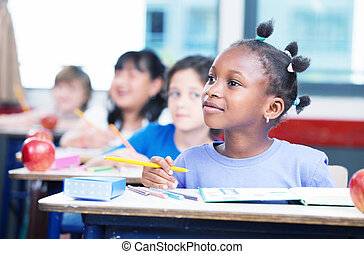 Row of students in a primary interracial classroom. Afro...