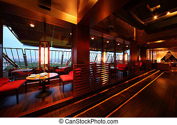 Row of tables and red seats with partition-walls in empty cozy restaurant at evening