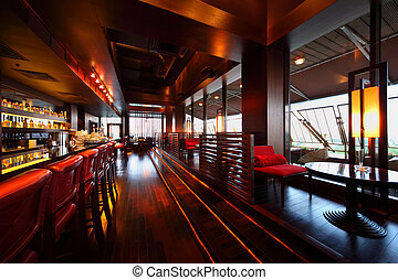 Row of tables, red seats and bar counter with red tall chairs in empty cozy restaurant
