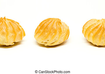 Row of three profiteroles isolated on the white background