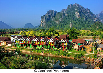 Row of tourist bungalows along Nam Song River in Vang Vieng, Vientiane Province, Laos. Vang Vieng is a popular destination for adventure tourism in a limestone karst landscape.