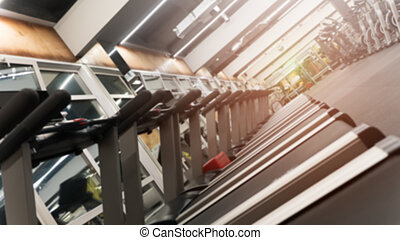 Row of treadmills in big new gym at angle