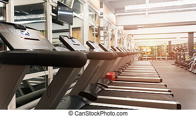Row of treadmills in big new gym without people
