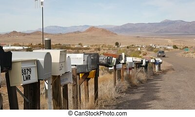 Row of vintage drop boxes on road intersection, arid Arisona desert, USA. Postal retro mailboxes on roadside of tourist Route 66. Address on old-fashioned nostalgic metal grunge postbox on pillar.