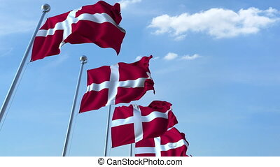 Row of waving flags of Denmark agaist blue sky, seamless loop