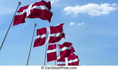 Row of waving flags of Denmark agaist blue sky, seamless loop