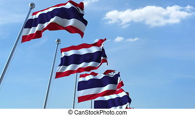 Row of waving flags of Thailand agaist blue sky, seamless loop