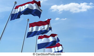 Row of waving flags of the Netherlands agaist blue sky, seamless loop
