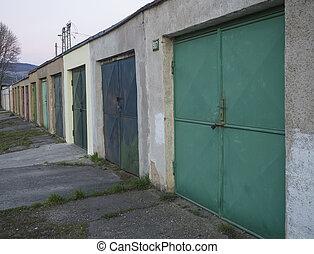 Row of weathered color old metal garage block doors, diagonal view
