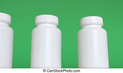Row of white bottles on green