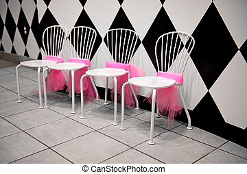 Row of White Chairs with Pink Ribbons