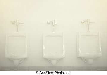Row of white urinals in men toilet