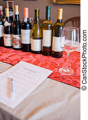 Row of Wine Bottles and a Glass by a Tasting Sheet