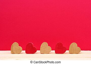 Row of wooden hearts against a red background