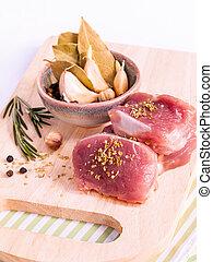Row pork tenderloin with herbs on cutting board. - Steak prepari