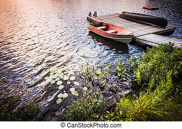 Rowboat at lake shore at sunrise