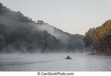 Rowboat on the lake at morning fog at Mae Hong Son or Pang Ung