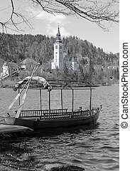 rowboats moored on the shore of Lake Bled in Slovenia in black a