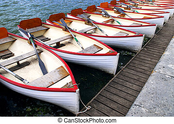 Row of docked wooden rowing boats for rent