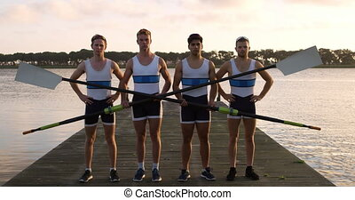 Rower male team looking at camera with oars in their hands...