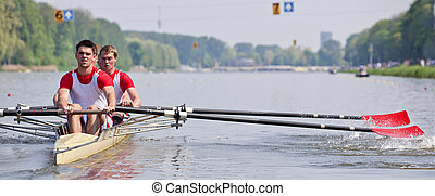 Rowers and oars - Oarsmen building up speed during a rowing...