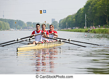 Rowers to the start - Coxed four rowing team paddling...